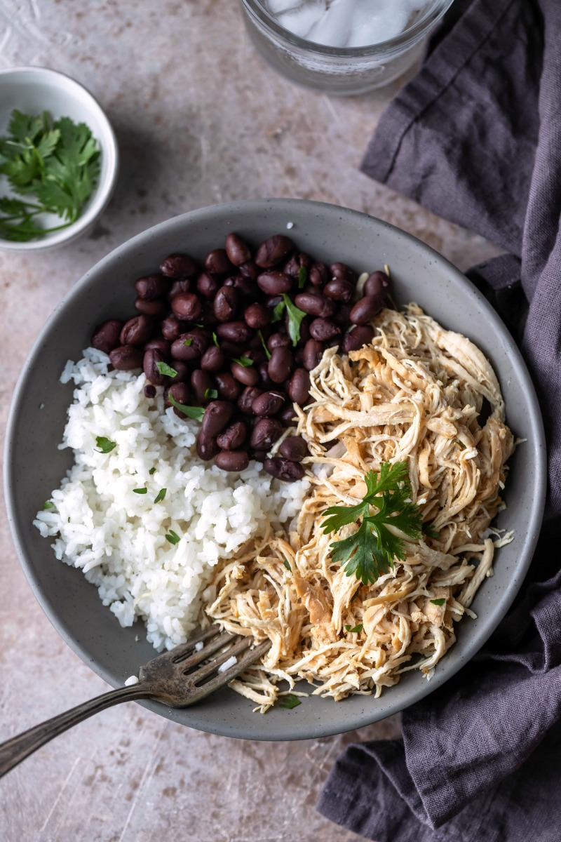 Shredded mojo chicken in a bowl with black beans and rice