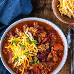 Bowl of instant pot chili topped with sliced green onions and shredded cheese
