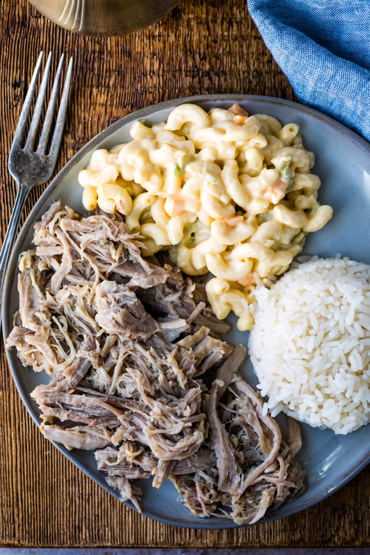 Overhead photo of shredded kalua pork next to macaroni salad and rice