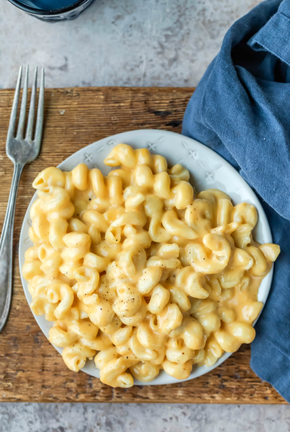 Plate of Instant Pot Macaroni and Cheese next to a blue linen napkin