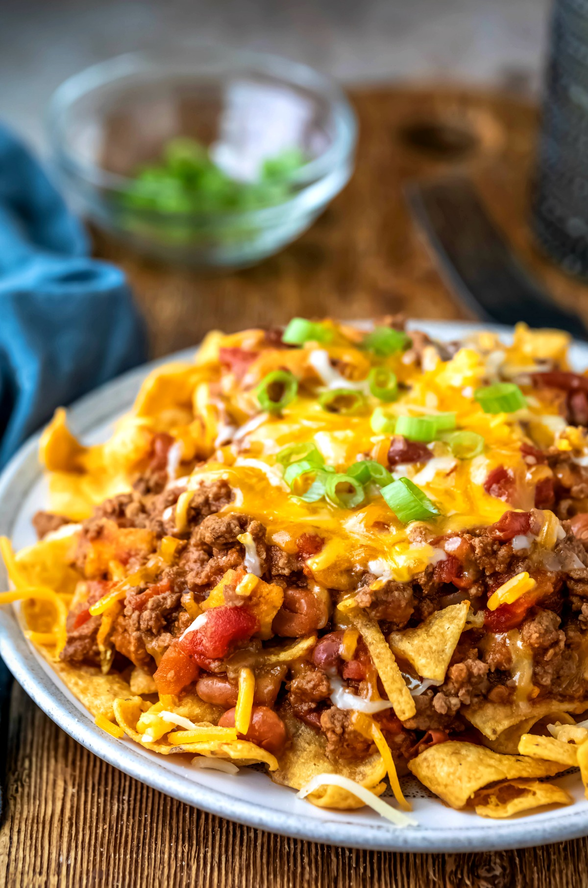 Frito chili pie topped with sliced green onions and melted cheese.