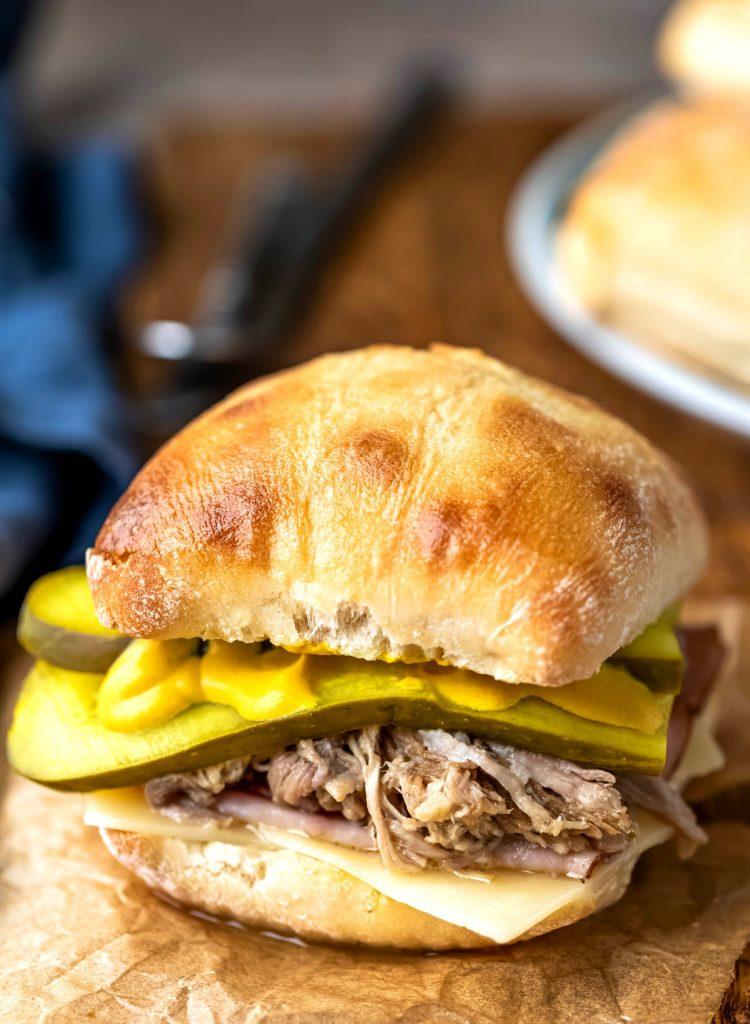 Cuban pork sandwich on a piece of brown parchment paper.
