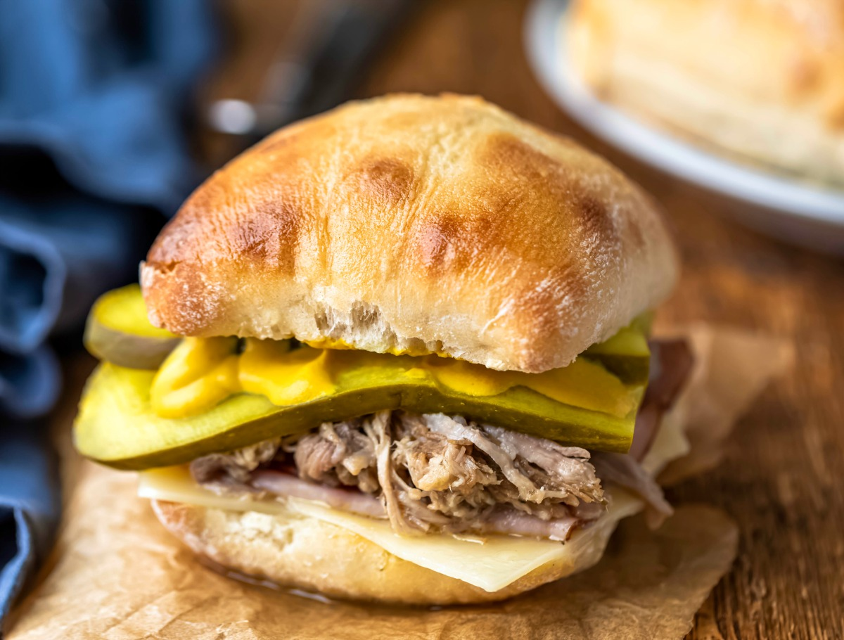 Cuban pork on a bun with ham and pickle slices