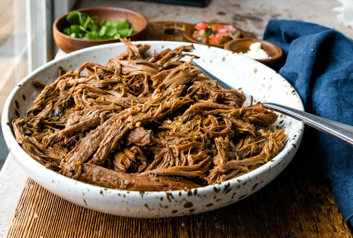 Dish of Instant Pot beef machaca on a wooden cutting board