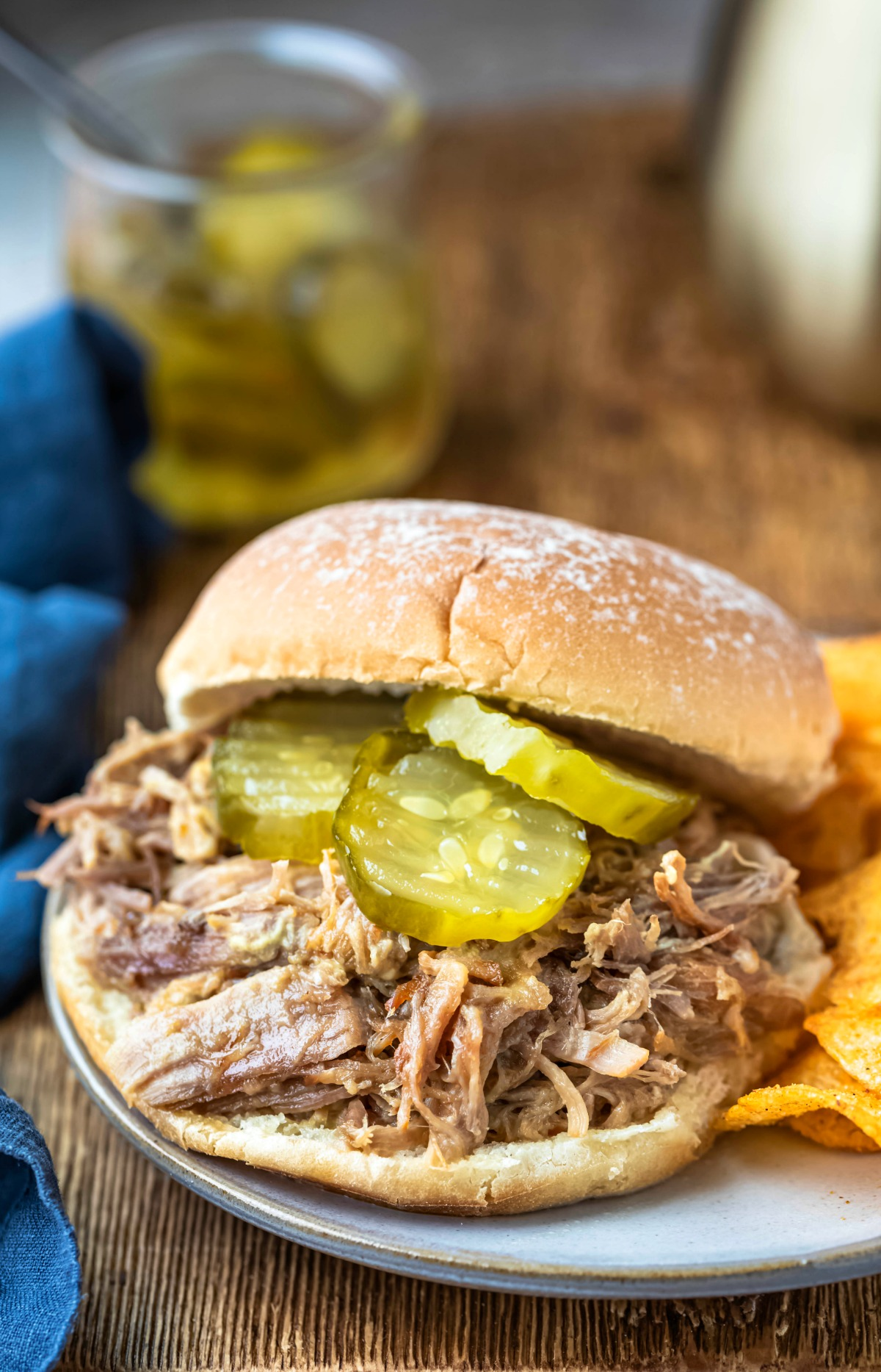 Instant pot honey mustard pork on a bun topped with pickle slices