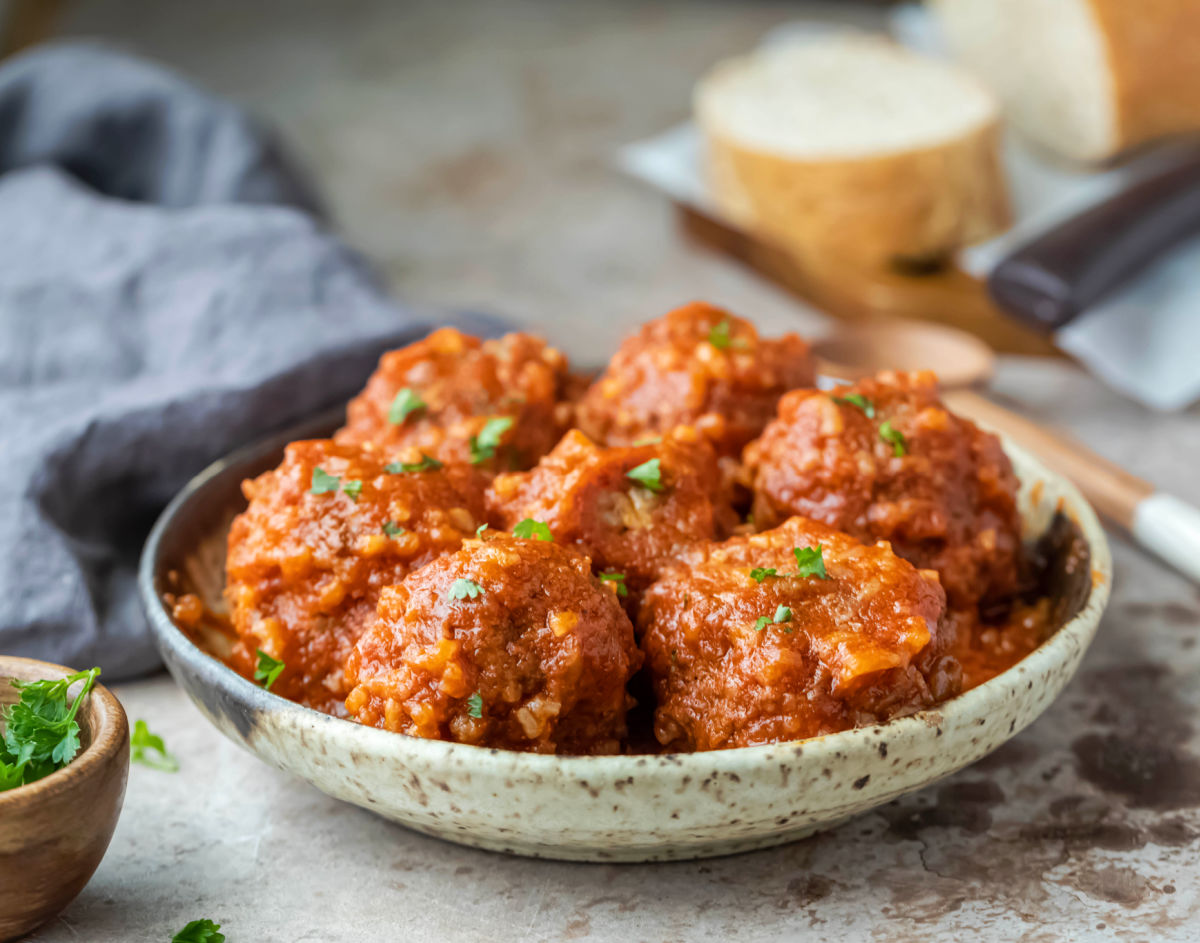 Dish of porcupine meatballs next to a wooden spoon