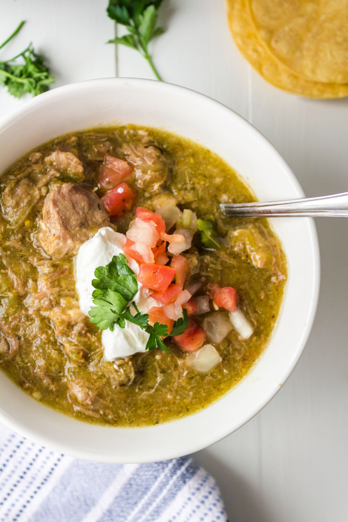 White bowl with pork chile verde in it