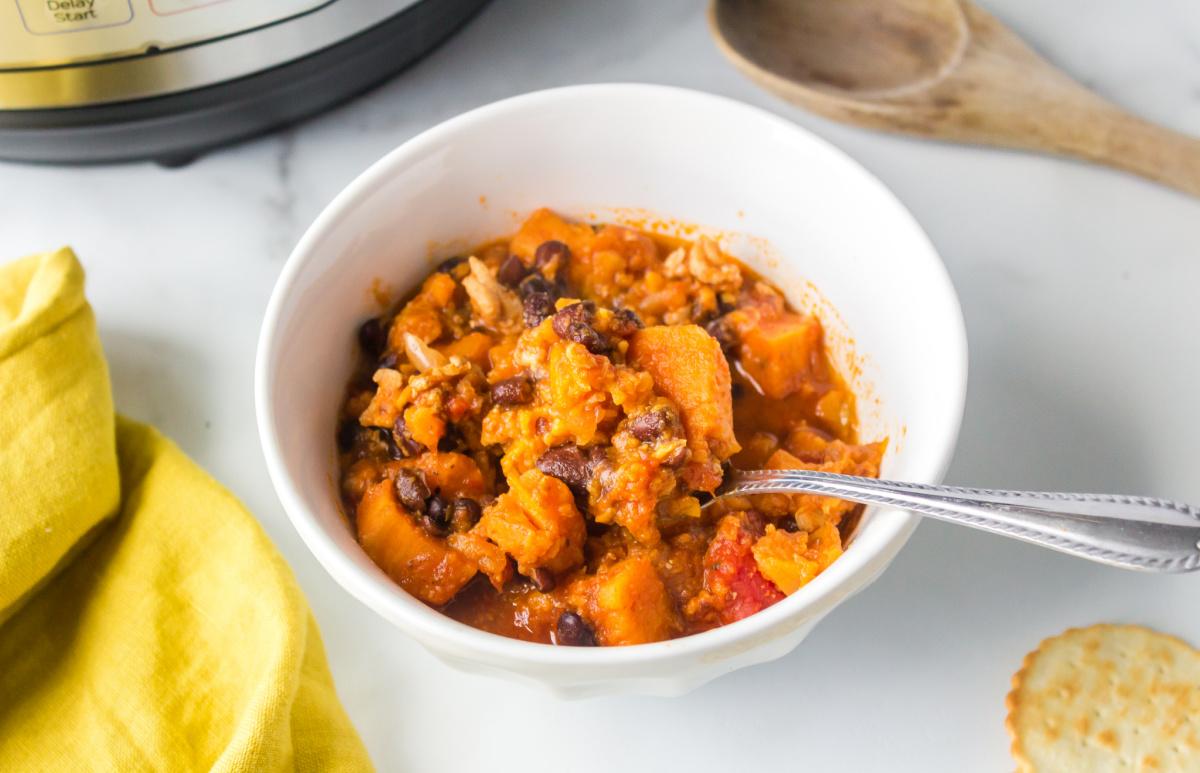 Bowl of turkey black bean sweet potato chili next to a yellow napkin