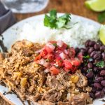 Plate with white rice, black beans, and mojo pork on it.