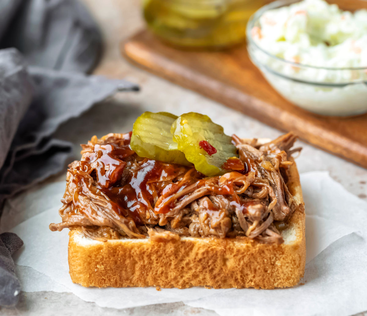 Beef brisket topped with barbecue sauce and pickle chips.