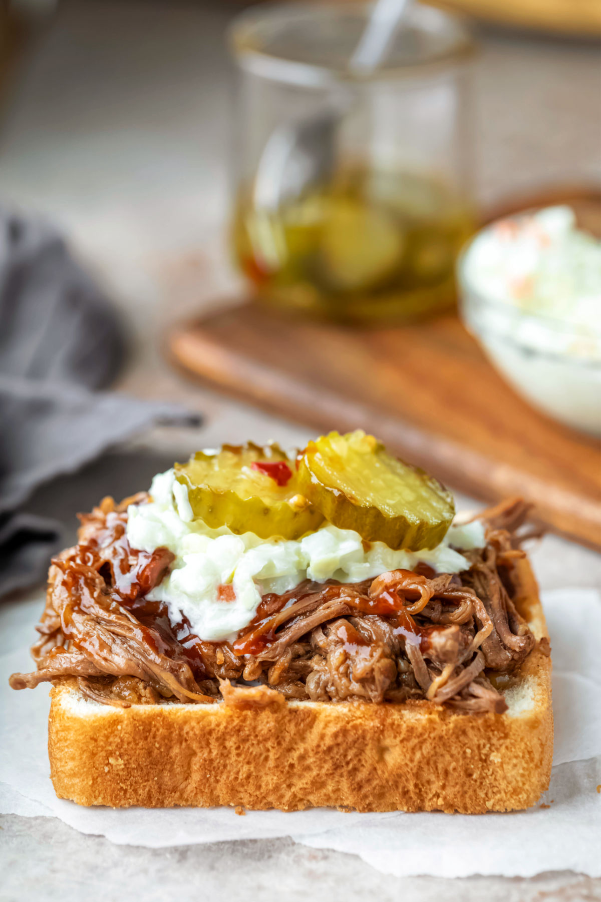 Beef brisket sandwich topped with coleslaw and pickle chips.